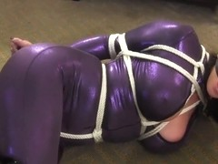 Christina Carter is wearing a sexy, spandex costume while getting tied up tight and gagged