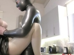 Latex Lucy is sucking a dildo while kneeling on the floor and then getting fucked hard