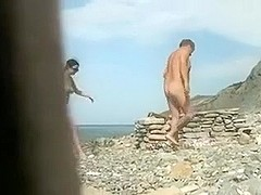 Spy cam clip with an amateur couple making love on a beach